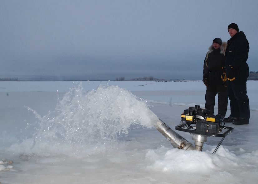 EIELSON AIR FORCE BASE, Alaska -- Master Sgt. Andy Harper and Tech. Sgt. Scott Fletcher, both from the 354th Civil Engineer Squadron, keep an eye on water being pumped from the river to build up the ice bridge. The ice bridge takes about five weeks to complete in sub-zero weather. It is five-foot deep, a mile long and capable of supporting more than 110 tons -- which completely vanishes a few months later. The ice bridge helps 354th CES members access and perform annual maintenance on Eielson's training and bombing ranges. (U.S. Air Force photo by Airman Jonathan Snyder).