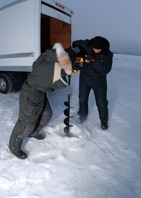 EIELSON AIR FORCE BASE, Alaska -- Master Sgt. Andy Harper and Tech. Sgt. Scott Fletcher, both from the 354th Civil Engineer Squadron, use an auger to measure the ice thickness. If the ice is not thick enough, water pumps will be placed in the drilled hole to help build the ice bridge. The ice bridge takes about five weeks to complete in sub-zero weather. It is five-foot deep, a mile long and capable of supporting more than 110 tons -- which completely vanishes a few months later. The ice bridge helps 354th CES members access and perform annual maintenance on Eielson?s training and bombing ranges. (U.S. Air Force photo by Airman Jonathan Snyder).