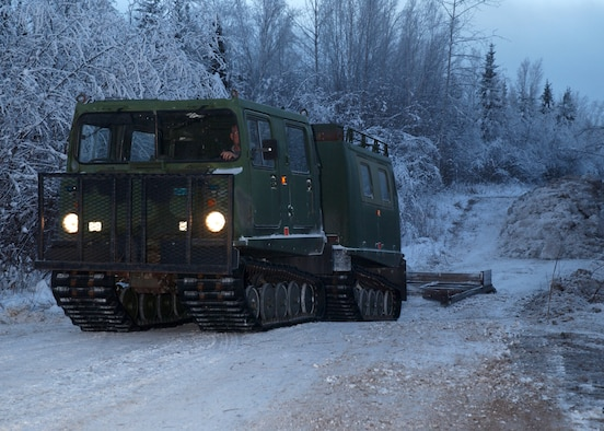 EIELSON AIR FORCE BASE, Alaska -- Timothy Ristow, 354th Civil Engineer Squadron, drives a Small Unit Support Vehicle with a grader to smooth out a road for access to the Blair Lake Bombing Range Facilities Dec. 13. The ice bridge takes about five weeks to complete in sub-zero weather. It is five-foot deep, a mile long and capable of supporting more than 110 tons -- which completely vanishes a few months later. The ice bridge helps 354th CES members access and perform annual maintenance on Eielson's training and bombing ranges. (U.S. Air Force photo by Airman Jonathan Snyder). (Released)