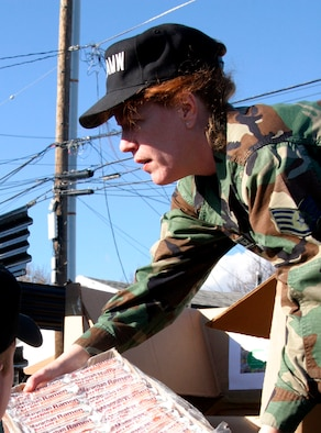 Staff Sgt. Rita Pfister, 349th Air Mobility Wing, helps load food for delivery during the 2006 Holiday Canned Food drive round up. The annual event allows Reserve Airmen from Travis Air Force Base to provide canned goods for those less fortunate.
