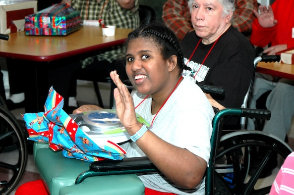 Waynetta Deolach, one of the 46 residents of the Grayson Square Health Care Center in San Antonio, waves thank you while opening up her Christmas present from members of the 737th Training Group at Lackland Air Force Base, Texas, and the Air Force Personnel Center. Members of the group and AFPC traveled to the Grayson Square Health Care Center Dec. 20 to participate in the annual holiday gift presentation. Group and AFPC personnel adopt the residents, who range in age from 21 to 103, and bring wrapped gifts to help brighten the residents' holidays. (USAF photo by Staff Sgt. Tim Russer)