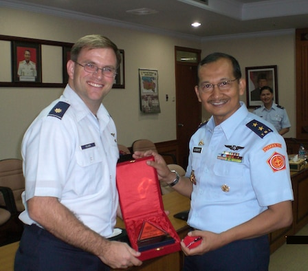"""JAKARTA -- Pacific Air Forces' International Health Affairs member, Maj Wesley Palmer, is presented a token of appreciation from Surgeon General of the Armed Forces of Indonesia, Air Vice Marshal (Dr.) A. Hidayatand.  Palmer was a guest speakers at the Indonesian Air Force's First """"Jakarta International Aerospace Medicine Symposium"""". In attendance were over 200 delegates from 5 countries.  (Photo courtesy of IHA)"""