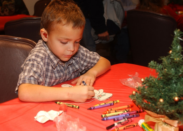 Devin Pitman, dependent of Tech. Sgt. Jeffrey Pitman of the 533rd Training Squadron, concentrates on his snowman paddle in the craft room at the Breakfast with Santa event December 16, 2006, in Vandenberg's Pacific Coast Club.  Devin was one of more than 1500 children and their parents in attendance.  The event is sponsored by the 30th Services Division annually and is open to all Vandenberg families.  (U.S. Air Force photo by Airman 1st Class Nicole Roberts)