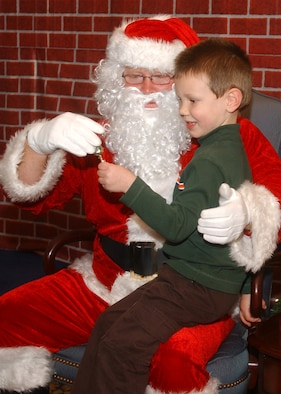 Alex Ammons, dependent of Master Sgt. Charles Ammons of the Mission Support Squadron, gets a treat from Santa after giving him his wish list at the Breakfast with Santa event December 16, 2006, at Vandenberg's Pacific Coast Club.  Alex was one of more than 1500 children and their parents in attendance.  The event is sponsored by the 30th Services Division annually and is open to all Vandenberg families.  (U.S. Air Force photo by Airman 1st Class Nicole Roberts)