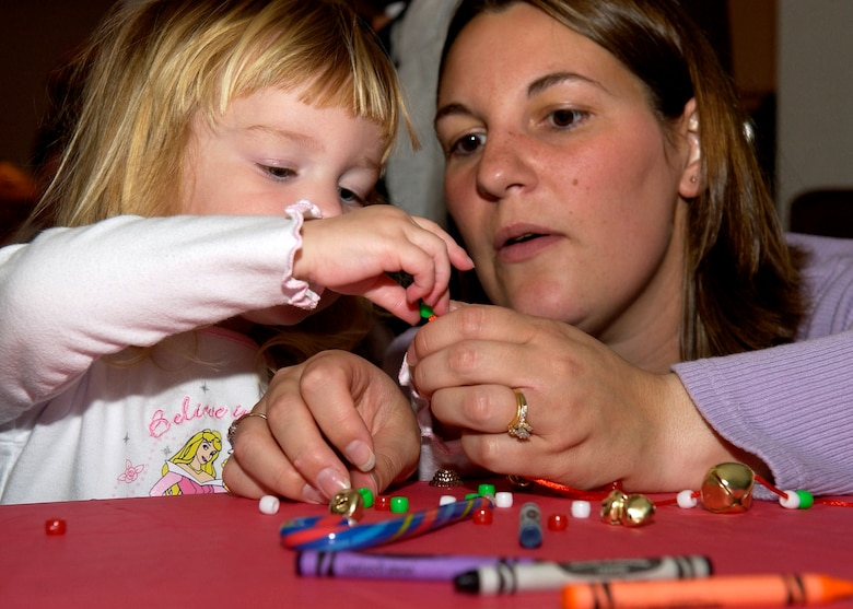 Kristin and Angie Brown, dependants of Tech.l Sgt. Jeff Brown, 30th Operations Support Squadron, make a necklace during the Breakfast with Santa event December 16, 2006, in Vandenberg's Pacific Coast Club.  Arts and crafts is one of the many events that took place as more than 1500 children and their parents filled the club for the 30th Services Division Sponsored event.  (U.S. Air Force photo by Airman 1st Class Stephanie Longoria)