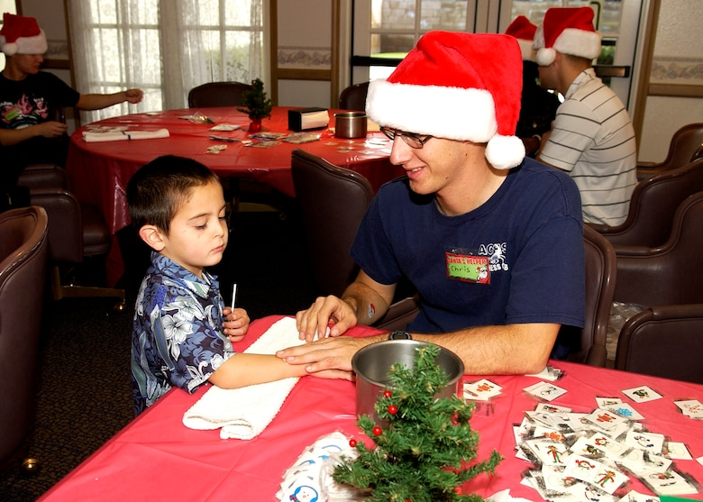 Airman Chris Herridge, 532nd Training Squadron, applies a removable tattoo to the arm of Dominic Daigle dependant of Senior Airman Shane Daigle, 576th Flight Test Squadron, at the Breakfast with Santa event December 16, 2006, in Vandenberg's Pacific Coast Club. More than 1500 children and their families filled the club for the 30th Services Division sponsored event.  (U.S. Air Force photo by Airman 1st Class Stephanie Longoria)