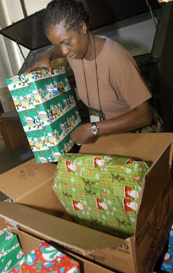 Maj. Gwen Taylor, 116th Logistics Readiness Squadron operations manager, packs presents into boxes to be distributed to families. U.S. Air Force photo by SUE SAPP