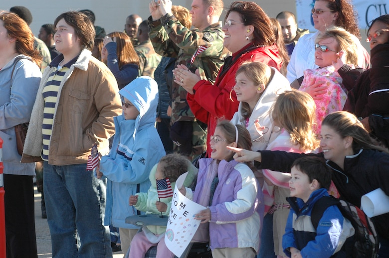 Family and friends of the returning Airmen show their excitement as the aircraft comes into view.