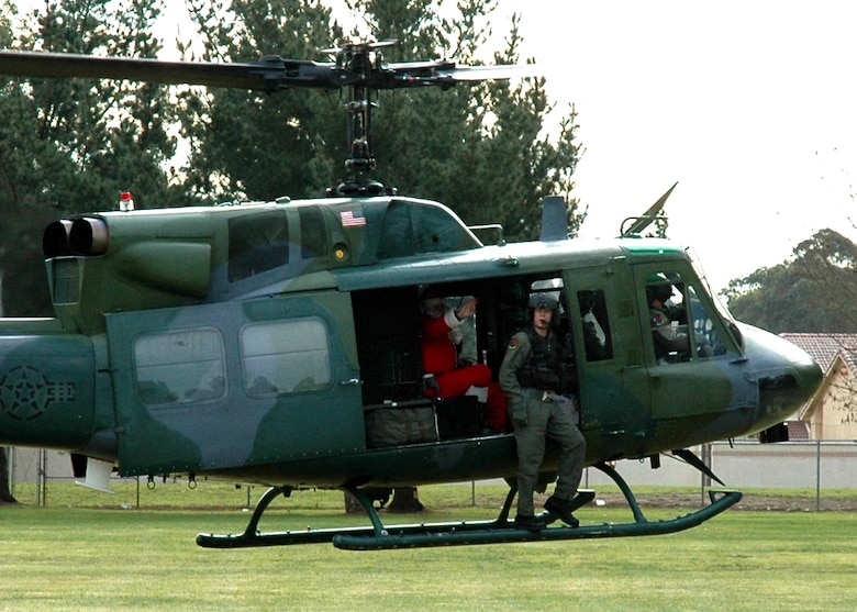 Santa waves to the students of Crestview Elementary School on Vandenberg Air Force Base, Calif., as his borrowed sleigh takes off.  Santa came to the school on a 76th Helicopter Squadron UH-1N Huey to present student representatives with bags of candy canes for their classrooms.  (U.S. Air Force photo by Staff Sgt. Raymond Hoy)