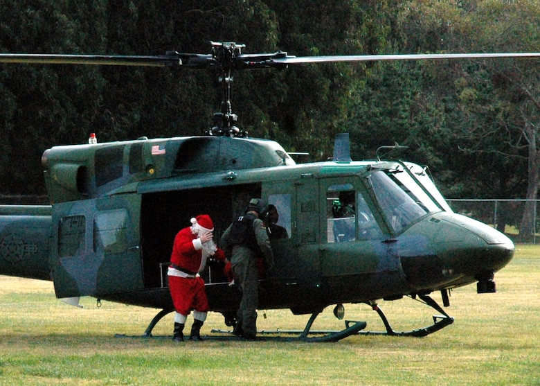 Santa steps out of a 76th Helicopter Squadron UH-1N Huey at Crestview Elementary School on Vandenberg Air Force Base, Calif.  Santa came to the school to present student representatives with bags of candy canes for their classrooms.  (U.S. Air Force photo by Staff Sgt. Raymond Hoy)