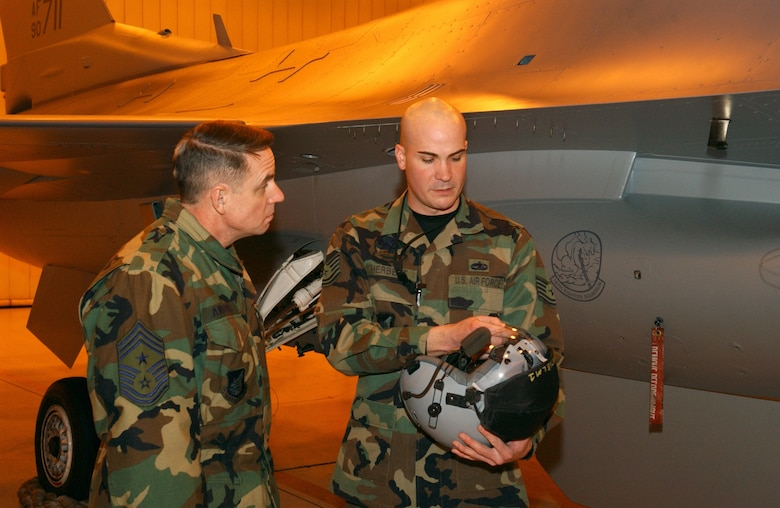 EIELSON AIR FORCE BASE, Alaska -- Technical Sergeant Peter Herbert, 354 AMXS/MXAFS, shows 11th Air Force Command Chief Master Sgt David Andrews a fighter pilots helmet on Dec 19. While visiting Eielson, Chief Andrews stopped by the 18th Aircraft Maintenance Unit for a tour of the building and an exclusive look at a F-16. 