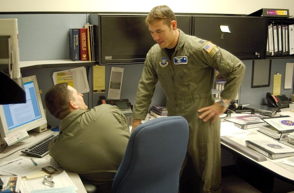 Capt. Alex Ruiz, 10th Missile Squadron, talks with 1st Lt. Ryan Durand about squadron operations Dec. 12.  Captain Ruiz will soon be trading in his flight suit for a stage costume as part of the Air Force Tops-In-Blue.