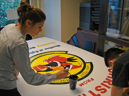 From left, 2nd Lt. Miriam Coleman and 1st Lt. Mu Jin Kim, 46th Test Squadron Detachment 1, apply the finishing touches on their unit's holiday card for the Hanscom Holiday Card Competition Dec. 14. Judges will choose first, second and third place winners Dec. 21. (U.S. Air Force photo by 2nd Lt. Brian P. Donnell)