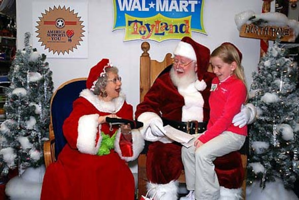 "Santa and Mrs. Claus open their gift from Sydney Spillane, 8, daughter of Senior Master Sgt. John Spillane, 29th Weapons School superintendent, during her trip to North Pole, Alaska, recently. Sydney and her parents, Tanya and Sergeant Spillane, won a trip to Santa's workshop and the first-ever ""Top of the World Toy Summit"" to test this year's hottest toys and visit with Santa. (Photo by Tanya Spillane)"