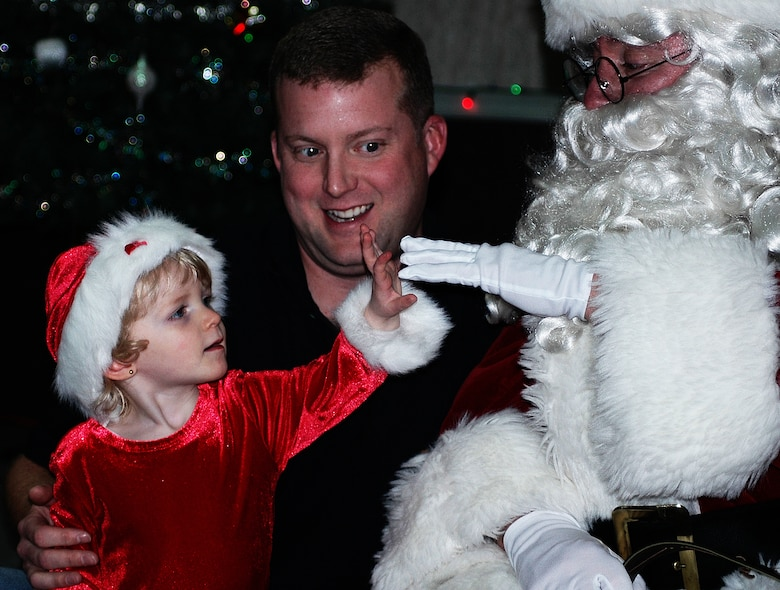 CHICOPEE, Mass. -- Tara Trudeau touches one of Santa Claus' white gloves during the Westover Christmas party held Dec. 9 for Westover Air Reserve Base families. Looking on is dad John Trudeau, an air reserve technician with Westover's 439th Maintenance Squadron. More than 40 children met with Santa during the annual party. The Pioneer Valley USO, located at Westover, manages the party each year. (US Air Force photo by Tech. Sgt. Andrew Biscoe)