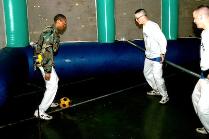 Two basic trainees from the 737th Training Group stand off against each other during a game of human foosball at the Basic Military Training Christmas Eve Extravaganza on Dec. 24 at Lackland Air Force Base, Texas. (USAF photo by Staff Sgt. Tim Russer)