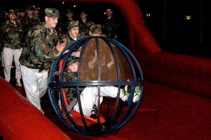 Airman Basic Peter Caruso from the 320th Training Squadron rolls down the human bowling alley, powered by his flight mates, during the Basic Military Training Christmas Eve Extravaganza on Dec. 24 at Lackland Air Force Base, Texas. (USAF photo by Staff Sgt. Tim Russer)
