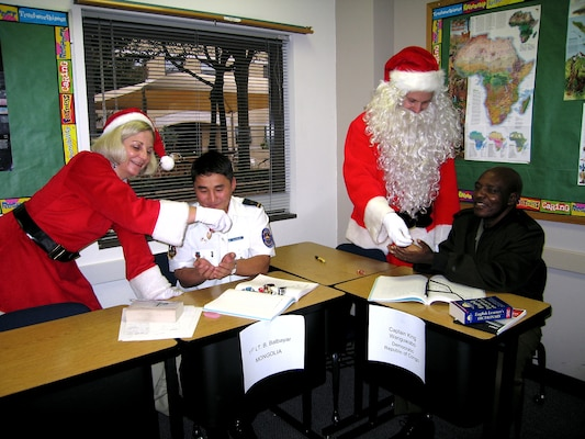 Santa and Mrs. Claus pay a visit to the Defense Language Institute English Language Center at Lackland Air Force Base, Texas, Dec. 21.  DLIELC international military students were surprised when the Clauses appeared in the classroom handing out candy. Before the candy was distributed, the students were asked if they had been good this year. (USAF photo by Annette D. Janetzke)