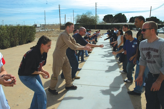 Sailors from the Branch Medical Clinic play a game called ?toss the egg? involving pairs of contestants who throw an egg back and fourth to each other while stepping back after each completed catch as part of the BMC?s 3rd Annual Super Bowl Tailgate  party Feb. 2 here.