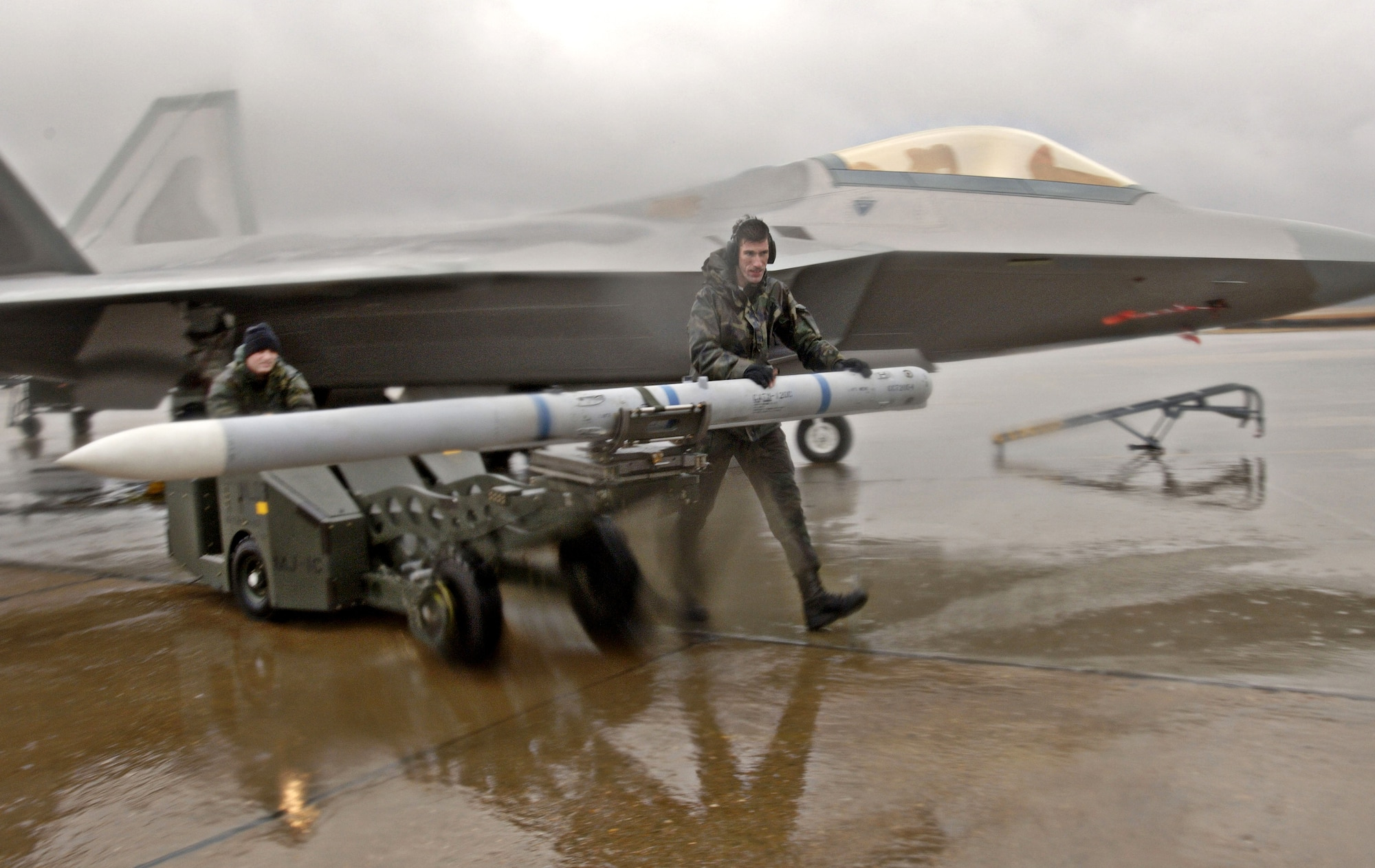 LANGLEY AIR FORCE BASE, Va. -- Senior Airman Michael Breed and Staff Sgt. Scott Robert walk through rain and strong winds with an AIM-120 missile. The missile was removed from an F-22A Raptor during the pre-generation portion of the Phase 1 operational readiness exercise here Jan. 31. (U.S Air Force photo by Staff Sgt. Eric T. Sheler)