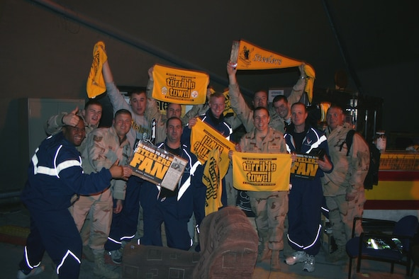 "MANAS AIR BASE, Kyrgyzstan -- Deployed Reserve members from the 911th Airlift Wing, Pittsburgh Air Reserve Station, celebrate their team's victory as the loudspeakers boom ""Pittsburgh's going to the Super Bowl!.""  They packed their ""Terrible Towels"" before deploying in hopes that the Steelers would do well in the playoffs. Preparation paid off. The Steelers went on to win Super Bowl XL, 21-10, over the Seattle Seahawks. (U.S. Air Force photo by Staff Sgt. Laura Gale)."