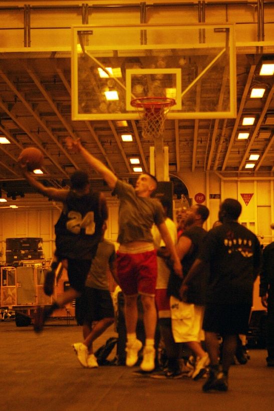 Marines and Sailors aboard the USS Iwo Jima during Expeditionary Strike Group/MEU Integration Training play basketball during their off time.  Marines have found that killing time aboard ship can be done by playing cards, competing in sports or reading books.