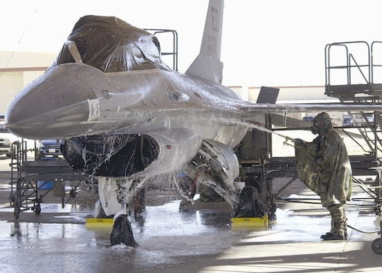 EDWARDS AIR FORCE BASE, Calif. (AFMCNS) — Members of the Joint Strike Fighter Integrated Test Force here prepare an F-16 for a final chemical decontamination test here Jan. 30. The F-16, used in place of an F-35, was sprayed with a chemical simulant, washed, then towed into a hangar and heated from 165- to 185-degree temperatures to accelerate the weathering of the remaining chemical. The goal of the testing is to decontaminate an entire aircraft to quickly return it to service should it be exposed to a chemical or biological agent. (Air Force photo by Mark McCoy)