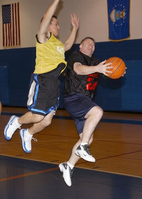 Ron Clark, 442nd Fighter Wing, (left) defends against Robert Schlatweiler, 509th Logistics Readiness Squadron, during the Whiteman Air Force Base Over-30 intramural basketball championship Feb. 8 at the fitness center. The 509th LRS won the game 45-40, ending a three-year championship reign by the 442nd Fighter Wing's team. The 442nd Fighter Wing is an Air Force Reserve unit based at Whiteman Air Force Base, Mo. (Photo by Senior Airman Ryan Wilson)