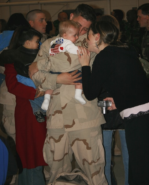 CANNON AIR FORCE BASE, N.M. -- Staff Sgt. Ryan Dobbel, 27th Civil Engineer Squadron, returns home to his wife, Jessica, and their 7-month-old daughter Taylor after a four-month tour in Southwest Asia. Over 100 27th Fighter Wing Airmen returned to Cannon Jan. 25. (U.S. Air Force photo by Airman Thomas Trower)