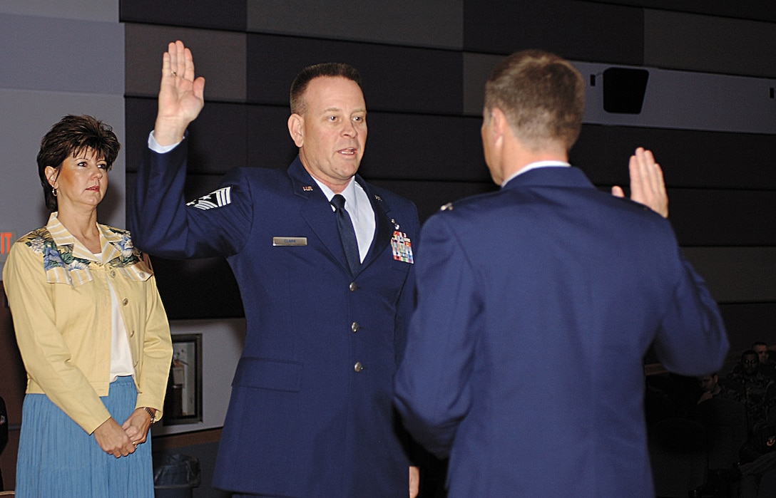 CANNON AIR FORCE BASE, N.M. -- Ms. Victoria Clark watches as Col. Jeff Harrell, 27th Fighter Wing vice commander, swears her husband,Chief Master Sgt. Ray Clark, in as the new 27th FW command chief. (U.S. Air Force photo by Tech. Sgt. Scott Mackay)