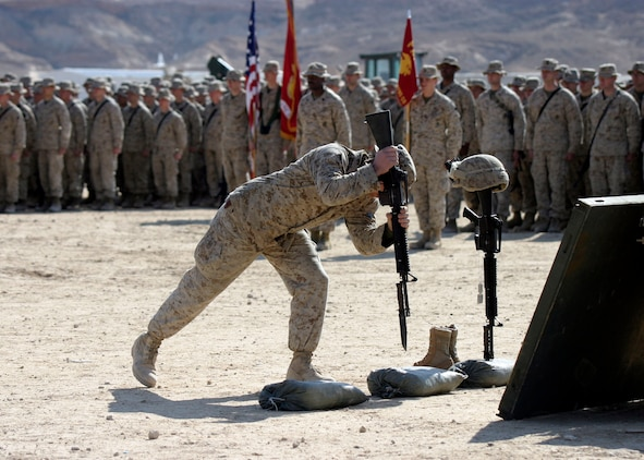 A Marine from Charlie Company, Battalion Landing Team 1st Bn., 2nd Marines, the ground combat element of the 22nd Marine Expeditionary Unit (Special Operations Capable), places a rifle in front of a memorial for Cpl. Orville Gerena, Lance Cpl. David Parr, and PFC Jacob Spann during a service held in their honor at Al Asad Air Base, Iraq Feb. 18, 2006.  The three Charlie Company Marines were killed conducting counterinsurgency operations in Iraq's Al Anbar province.