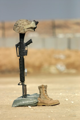 Boots, rifle, dog tags, and kevlar helmet stand in solitude to honor Cpl. Orville Gerena, Lance Cpl. David Parr, and PFC Jacob Spann during a sevice held by Battalion Landing Team 1st Bn., 2nd Marines, the ground combat element of the 22nd Marine Expeditionary Unit (Special Operations Capable), at Al Asad Air Base, Iraq Feb. 18, 2006. The three Charlie Company Marines were killed conducting counterinsurgency operations in Iraq's Al Anbar province.