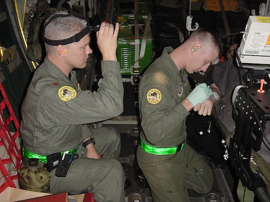 Critical Care Air Transport Team nurse Maj. Rodney Logan, 60th Medical Operations Squadron, sheds a little light for Tech. Sgt. William Webster, a cardiopulmonary CCATT member, as he administers to a Hurricane Katrina evacuee during an aeromedical evacuation mission aboard a C-130 Hercules in September 2005. (U.S. Air Force photo by Dr. [Maj.] Lazaro Bravo)