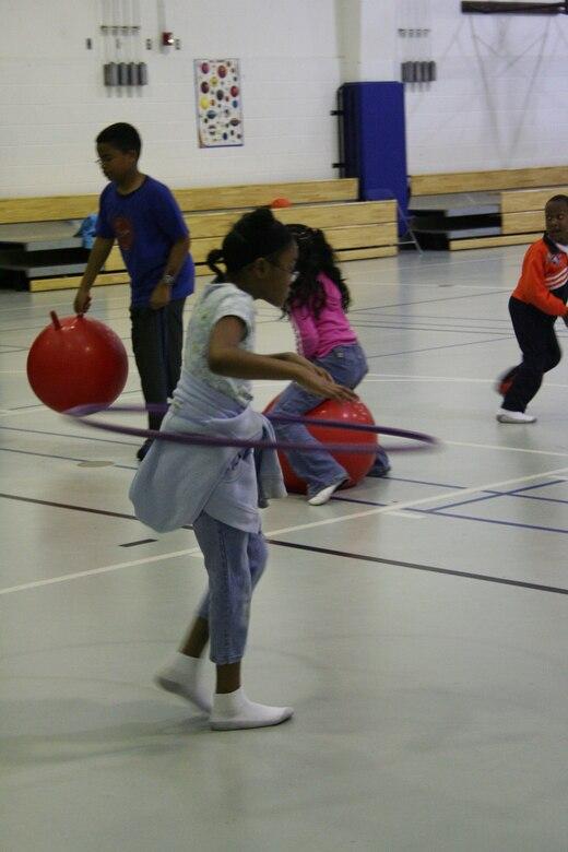 Indya Drew hula hoops her way across the gym floor at the Hurlburt Field youth center