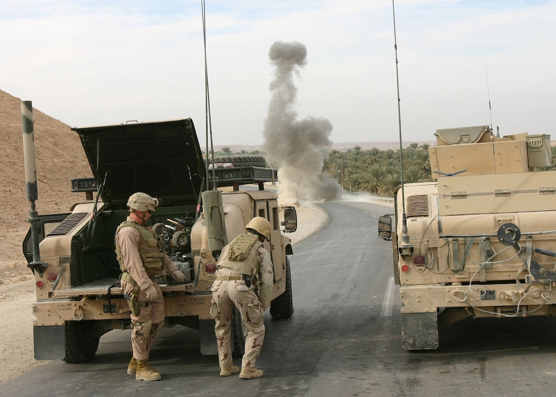 Members of a Navy and Marine Explosive Ordnance Disposal (EOD) supporting a patrol from Battalion Landing Team 1st Bn., 2nd Marines take cover behind their Humvee as they destroy an improvised explosive device near Forward Operating Base Hit, Iraq, Jan. 2, 2006.  The patrol, which is part of the ground combat of the 22nd Marine Expeditionary Unit (Special Operations Capable), moments earlier discovered the IED and also engaged and destroyed an insurgent IED placement team as part of the MEU's ongoing counterinsurgency efforts in Iraq's Al Anbar province with the 2nd Marine Division.