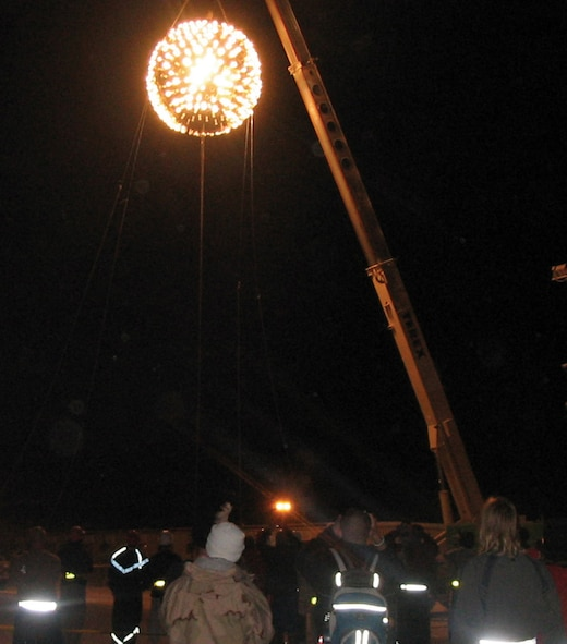 SOUTHWEST ASIA (AFPN) -- A 2,000-pound New Year's Eve Ball lights up the sky over this desert base. The ball, sculpted from a sewage tank, was the work of 379th Expeditionary Civil Engineering Squadron. They built it in about 72 hours. It was suspended approximately 100 feet in the air and lowered from a crane as the crowd counted down the seconds until 2006. (U.S. Air Force photo)