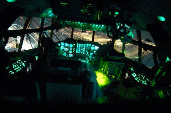 OVER BALAD AIR BASE, Iraq (AFPN) -- In the shadows of their C-130 Hercules' flight deck, (left to right) pilot Maj. Mike Wilson, flight engineer Senior Master Sgt. Ernie Leyba and co-pilot Capt. Tim Pemberton approach for a landing at Balad Air Base. The crew flew a New Year's Eve mission to deliver 13 passengers and 13,000 pounds of cargo -- landing at Balad in 2006. Members of the Air Force Reserve Command's 731st Airlift Squadron, the crew is ending a Southwest Asia tour with the 746th Expeditionary Airlift Squadron. (U.S. Air Force photo by Master Sgt. Lance Cheung)