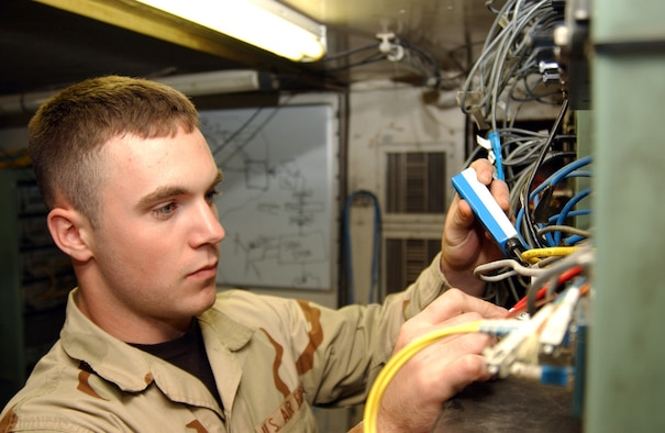 BALAD AIR BASE, Iraq (AFPN) -- Airman 1st Class Josh Green checks the wires on a system in the Kingpin communications tent. He is with the 727th Expeditionary Air Control Squadron. (U.S. Air Force photo by Senior Airman Bryan Franks)