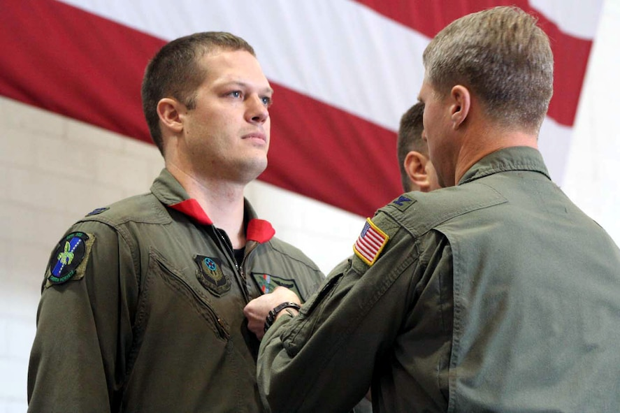 Capt. Matthew Berry, 20th Special Operations Squadron, receives his Distinguished Cross with Valor from Col. Mark Alsid, 20th SOS commander, during a ceremony Dec. 16 in Freedom Hangar. (U.S. Air Force photo by Senior Airman Heidi Davis)