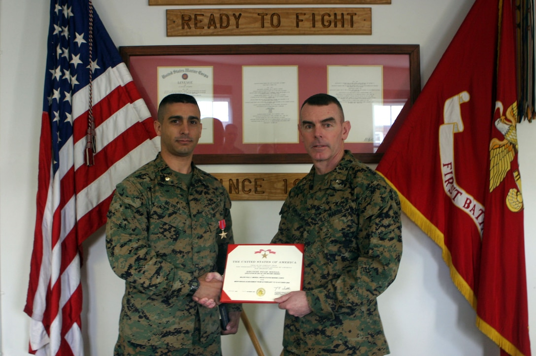 MARINE CORPS BASE CAMP LEJEUNE, N.C.- Maj. Paul C. Merida, from Pittsburgh, Penn., is awarded his second Bronze Star Medal from Brig. Gen. Joseph J. McMenamin, assistant division commander, in a ceremony here. Merida was the operations officer of 1st Battalion, 6th Marine Regiment in support of Operation Iraqi Freedom from February to October 2005.
