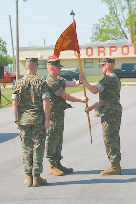 Capt. Robert Walker, the new commanding officer of Marine Air Control Squadron 2, Detachment A, passes the unit guidon to Master Sgt. Mark Kayser, the Det.?s staff noncommissioned officer-in-charge, as Capt. Christopher Coble, the outgoing CO of MACS-2, stands by May 10.