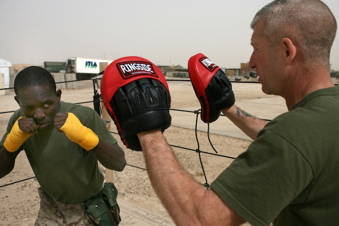 Twenty-one-year-old Shreveport, La. resident, Cpl. Sebastian B. Price trains with hand tape and focus mitts with the help of Sgt. Rich F. Litto, March 10, at Camp Mercury, Iraq.  Two former professional boxers from Boston donated a shipment of boxing equipment to 3rd Battalion, 5th Marine Regiment to support Marines in the fight against terrorism.