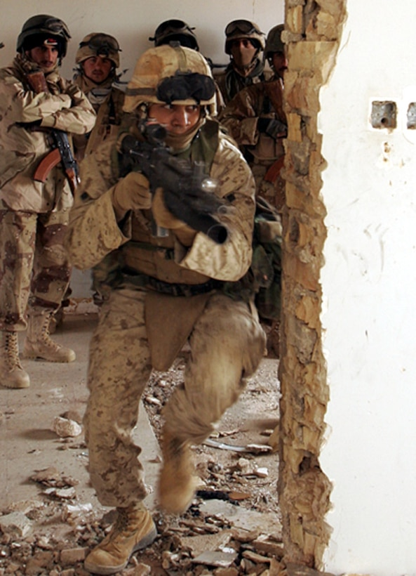 Lance Cpl. Jose D. Hernandez, a 21-year-old Los Angeles native and scout team leader, Company D, 1st Light Armored Reconnaissance Battalion, demonstrates to a group of Iraqi soldiers the proper technique for a one-man room clearing near Camp Korean Village. Hernandez his teammates, and the Iraqis were performing pre-combat rehearsals prior to a raid on a gas station. Marines are increasing the amount of time spent training their Iraqi counterparts to enhance the Iraqis' ability to fight the insurgency with minimal American assistance.