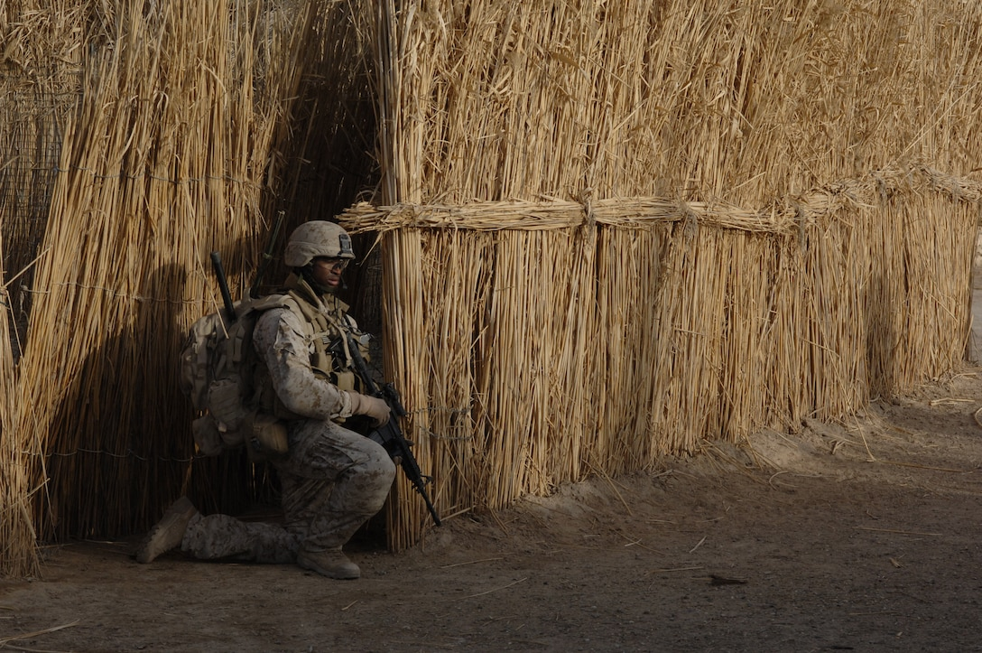 Camp Corregidor, Al Anbar, Iraq. (May 13, 2006) Corporal Julius Mitchell attached to the Marine Corps 2nd Air Naval Gunfire Liaison Company (ANGLICO) scans his sector while on patrol in the city of Ramadi. The mission was part of the continuing support of the 2-28 BCT. 2-28 BCT is deployed with IMEF (FWD) in support of Operation Iraqi Freedom in the Al Anbar province of Iraq (MNF-W) to develop the Iraqi security forces, facilitate the development of official rule of law through democratic government reforms, and continue the development of a market based economy centered on Iraqi reconstruction. U.S Navy Photo by Photographers Mate Second Class Samuel C Peterson (Released)