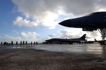 ANDERSEN AIR FORCE BASE, Guam (AFPN) -- Airmen conduct a foreign object damage walk on the flightline before a morning sortie here. The Airmen, from the 28th Bomb Wing at Ellsworth Air Force Base, S.D., are here for an air expeditionary deployment. They provide the U.S. Pacific Command a continuous bomber presence in the Asia-Pacific region. (U.S. Air Force photo by Master Sgt. Val Gempis)