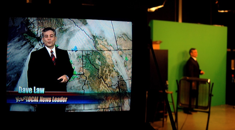 """FAIRCHILD AIR FORCE BASE, Wash. (AFPN) -- Retired Master Sgt. Dave Law, broadcast weatherman, KHQ6, uses a """"clicker"""" to switch backgrounds from one image to another during the course of his broadcast Jan. 6. He knows how much time is left by queues from the producer he receives through an earpiece. Dave Law retired from the Air Force in November after serving 23 years as a meteorologist. (U.S. Air Force photo by Staff Sgt. Nathan Gallahan)"""