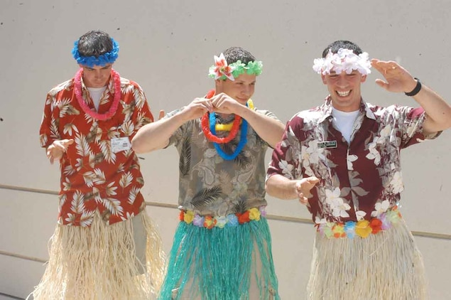 Petty Officer 2nd Class Andy Wilson (left), clinic pharmacy technician, Seaman Cody Weruen (center), clinic military medicine, and Petty Officer 3rd Class Benjamin Reyes, station corpsman, compete for hula dancing champion bragging rights. Reyes danced away as the champion saying the competition made him feel more like a man. The event also featured hula-hoop and ugliest Hawaiian T-shirt contests, new staff recognition and a presentation for a future sailor.