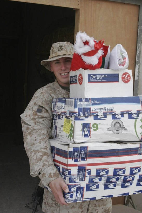 051225-M-2607O-001 - Seman Apprentice Kyle C. Mallard, Religious Program Specialist for 2nd Battalion, 2nd Marine Regiment, carries some packages filled with stocking to be loaded on a convoy for the Marines in the area of operation.