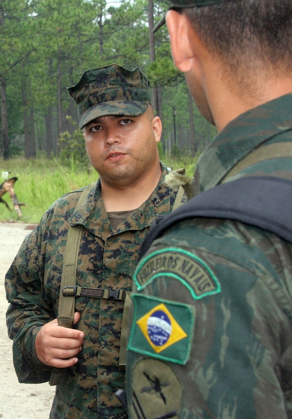 MARINE CORPS BASE CAMP LEJEUNE, N.C. - Cpl. Antonio A. Zugno, a rifleman with Company F, 2nd Battalion, 24th Marine Regiment, 4th Marine Division, fields a question from one of the Brazilian Marines. Zugno, who was born in Porto Alegre, Brazil, served as the battalion's translator while a group of Brazilian Marines from Rio de Janeiro, Brazil, joined them during their two weeks of annual training. The reserve unit is based out of Milwaukee.