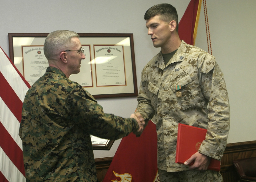 MARINE CORPS BASE CAMP LEJEUNE, N.C. - Maj. Gen. Richard A. Huck, 2nd Marine Division's commanding general, left, congratulates Sgt. Aaron C. Torian of 2nd Reconnaissance Battalion for being appointed as the Division NCO of the Year for 2005.  Torian, a 28-year-old Paducah, Ky. native, distinguished himself as a team leader while conducting counterinsurgency operations during Operation Phantom Fury in Fallujah, Iraq in late 2004.